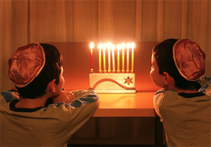2 boys looking at a menorah