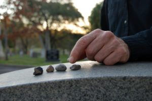 hand placing stones on a headstone