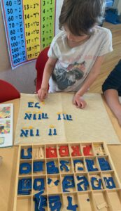 student doing puzzles with Hebrew letters
